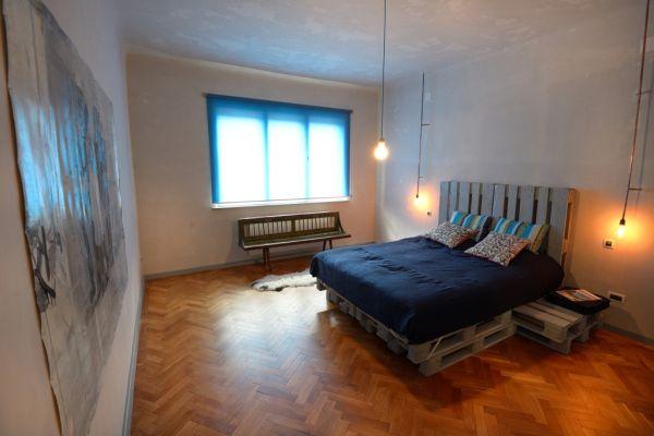 Cudowne łóżko palet we wnętrzu sypialni
